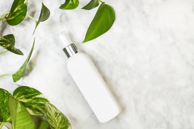 Бутылка крема для тела на мраморном столе с зелеными листьями