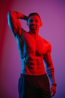 あごひげを生やしたボディービルダーは、青と赤の光の下で頭の後ろに筋肉の腕を持ってポーズをとっています