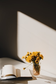本と黄色いタンポポの束