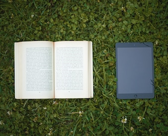 A book and a tablet on the grass