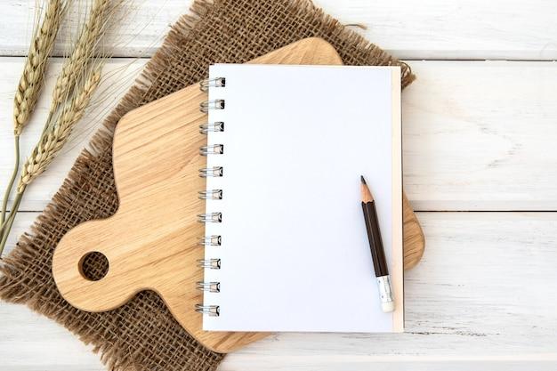 白いテーブル上のカッティングボードとテーブルクロスを切り刻むノートブックのノート紙