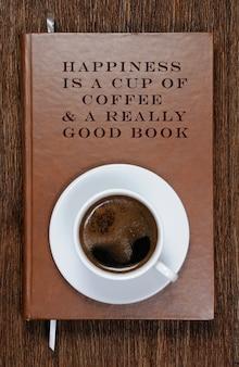 やる気を起こさせる引用と一杯のコーヒーが入った本