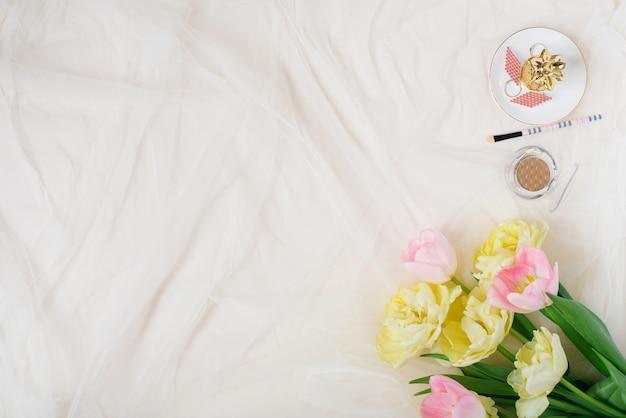 Граница из розовых цветов желтых тюльпанов, аксессуаров и косметики на заднем плане .. макет женского домашнего офиса. плоская планировка, вид сверху.