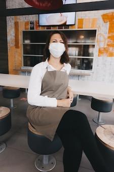 앞치마와 의료용 마스크를 쓴 지루한 웨이트리스가 카페 바에 앉아 있습니다. 손님을 방문하지 않는 커피숍의 주인. 사업.