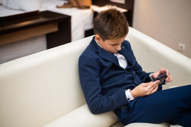 Скучающий мальчик в официальной одежде сидит на диване и смотрит в свой телефон.