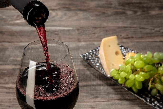 木製のテーブルの上にフルーツと赤ワインのボトルとグラス