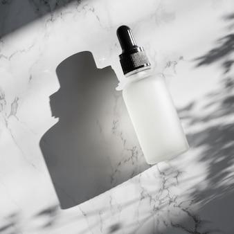 Флакон сыворотки с гиалуроновой кислотой на мраморном фоне с резкой тенью.