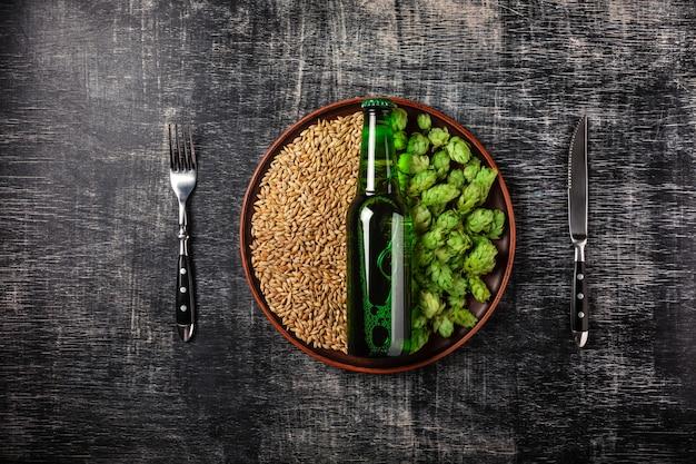 Бутылка пива на зеленом свежем хмеле и зерна пшеницы в тарелке на фоне черной поцарапанной доске