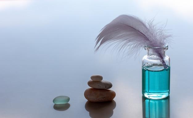 Бутылка ароматизированного синего масла и липкое птичье перо. пирамида из камней и стекла складывается. синий размытый фон. место для текста.