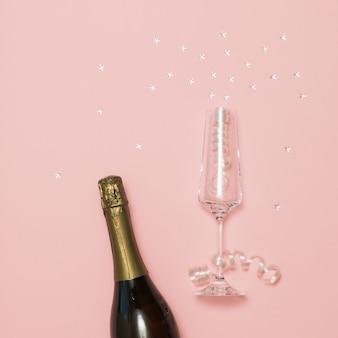 ピンクの背景にシャンパンのボトルと崩れかけたスパンコールのグラス。シャンパングラスでお祭りの背景。