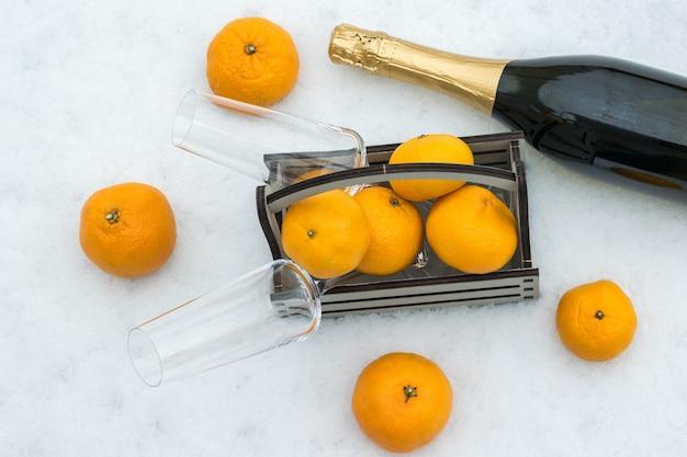 Бутылка шампанского и деревянный ящик с мандаринами в снегу.