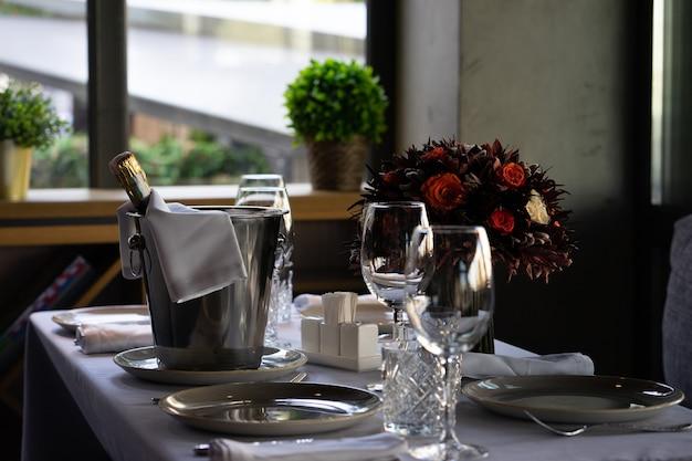 여러 손님을 위해 카페 또는 레스토랑 테이블에 얼음 양동이에 샴페인 또는 스파클링 와인 한 병. 필드의 얕은 깊이, 배경을 흐리게