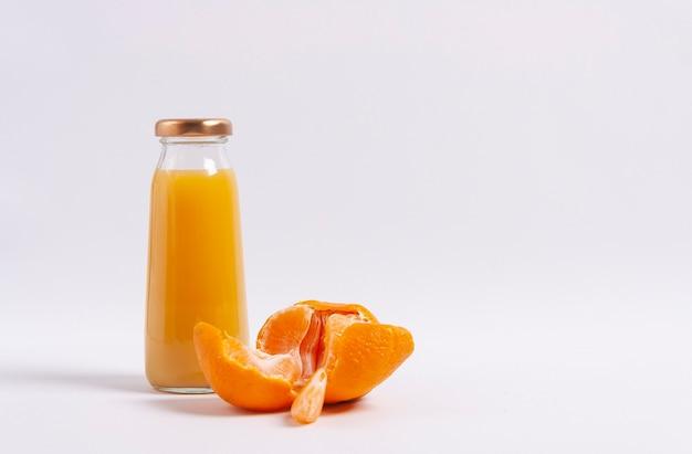 白い背景の上の柑橘類のジュースのボトル。水平方向。