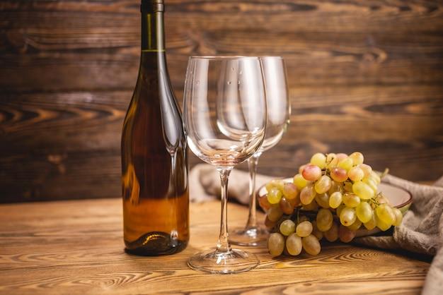 유리와 나무 테이블에 포도의 무리와 함께 드라이 화이트 와인 한 병