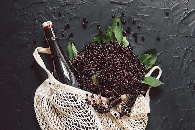 Бутылка сиропа бузины на темном фоне со свежими ягодами бузины и авоськой.
