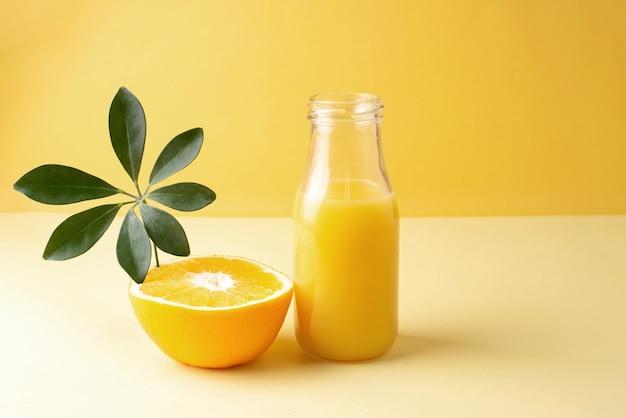 新鮮なオレンジジュースのボトルとオレンジの半分。
