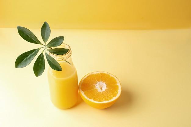 緑の葉とオレンジの半分が入った新鮮なオレンジジュースのボトル。