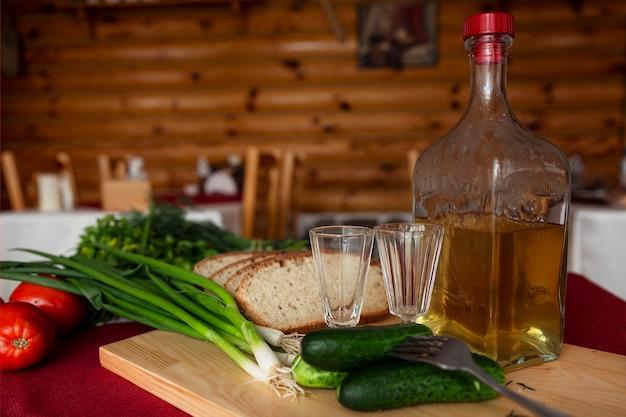 Бутылка домашней водки, стаканы и свежие овощи с хлебом на столе в деревянном деревенском доме. русские традиции.