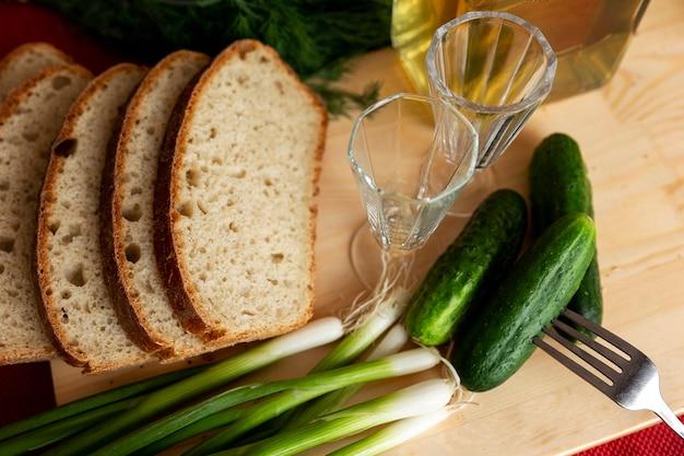 Бутылка домашней водки, стаканы и свежие овощи с хлебом на столе. русские традиции.