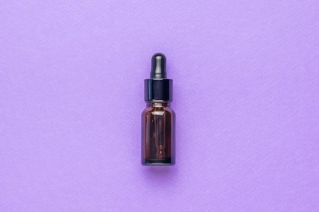 Бутылка лекарства из темного стекла на фиолетовом фоне. концепция лечения и ухода за телом с помощью натуральных средств. плоская планировка.
