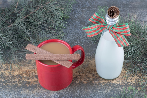 Бутылка молока с бантом и стеклом на мраморном фоне. фото высокого качества