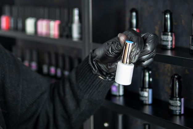 Бутылка лака для ногтей в руке женщины. выбрать цвет лака для ногтей. мастер маникюра открывает бутылку лака для ногтей. набор различных лаков для ногтей на полках в косметическом магазине.