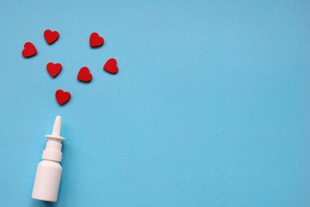 Бутылка назального спрея на синем фоне и красные сердца вокруг нее