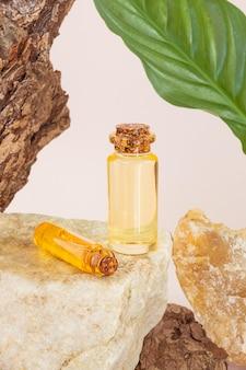 아름다운 질감과 잎을 가진 나무 껍질 옆에있는 돌에 천연 에센셜 오일 한 병. 천연 에센스, 유기농 화장품, 아로마 테라피, 스파에 대한 개념.