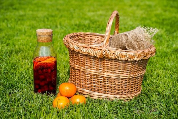 ベリーとオレンジの純粋な有機食品と飲み物を素朴なスタイルのオレンジジュースに入れた天然の自家製ソーダのボトルと緑の草の上のバスケット