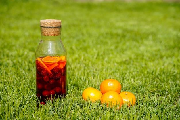 緑の草の上に素朴なスタイルのオレンジジュースでベリーとオレンジの純粋な有機食品と飲み物を含む天然自家製ソーダのボトル