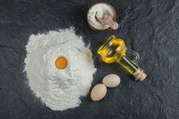 小麦粉と生卵黄の木製ボウルとオイルのボトル。