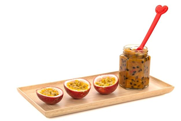 나무 쟁반에 열정 과일이 반으로 쪼개진 열정 과일 잼 한 병.