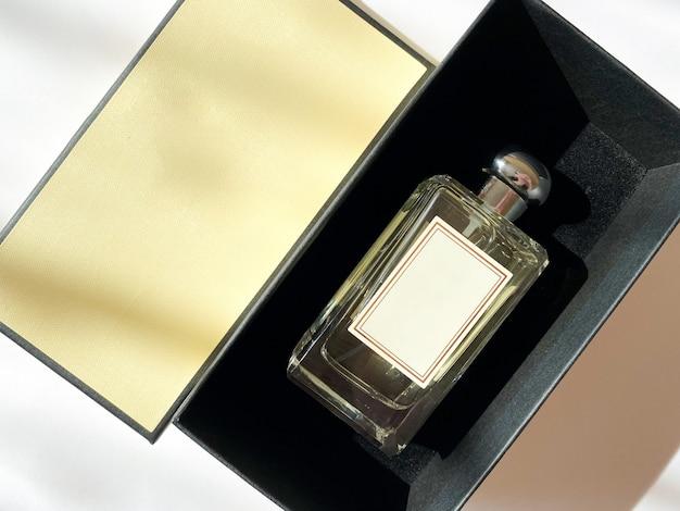 Флакон духов из желтой коробки на белом изолированном фоне