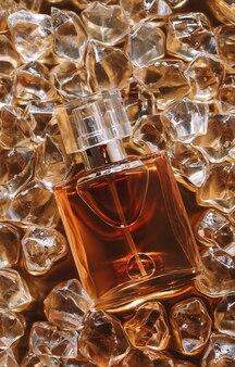 氷の上の香水のボトル、オードトワレ、水滴。ホットアイスのコンセプト