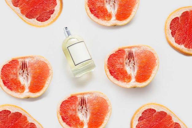 グレープフルーツパターンの壁に、白い壁に香水またはオイルのボトル。フレグランス、柑橘類の成分、アロマセラピー、またはアロマティックグレープフルーツオイルの概念的な構成。
