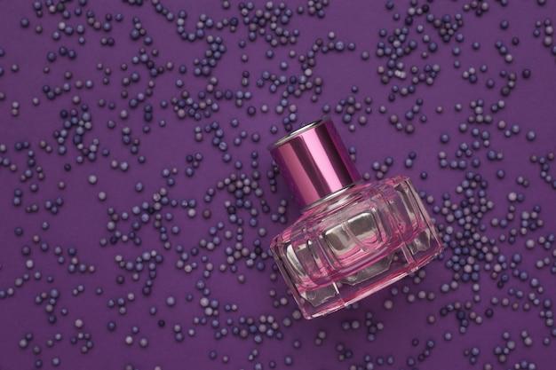 Флакон духов над фиолетовыми шарами на фиолетовом столе. ароматическая жидкость.