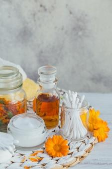 ポットマリーゴールドチンキまたは輸液、軟膏、クリームまたは香油のボトル。新鮮で乾燥したキンセンカの花とコットンパッドを白に貼り付けます。天然の薬草。