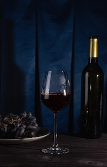 Бутылка красного вина, бокал и виноград на темном фоне.