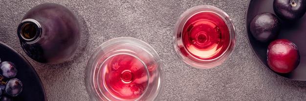 テクスチャードテーブルの赤ワインとフラットレイグラスプラムのボトルは、灰色のコンクリートのヘッダーです...