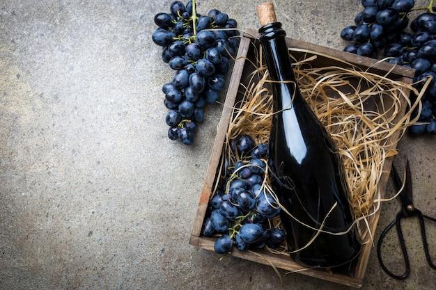 灰色の石の上にブドウが入った箱に入った赤ワインのボトル