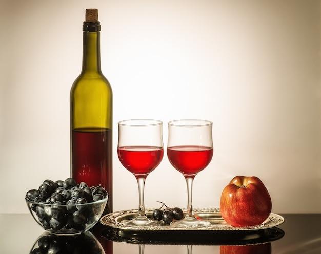 레드 와인의 병 두 잔 사과와 포도 테이블에 서있는 컵