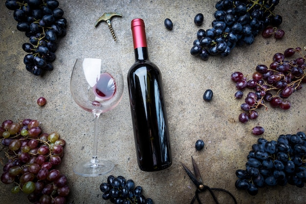灰色の石の上にガラスとブドウと赤ワインのボトル