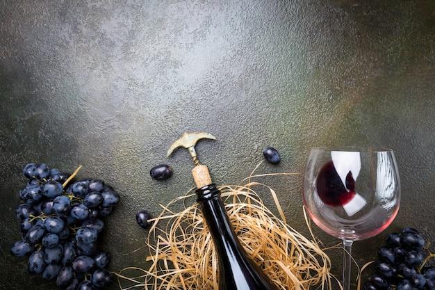 暗い石の上にガラスとブドウと赤ワインのボトル