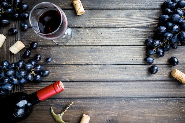 木製の上にガラスとブドウと赤ワインのボトル
