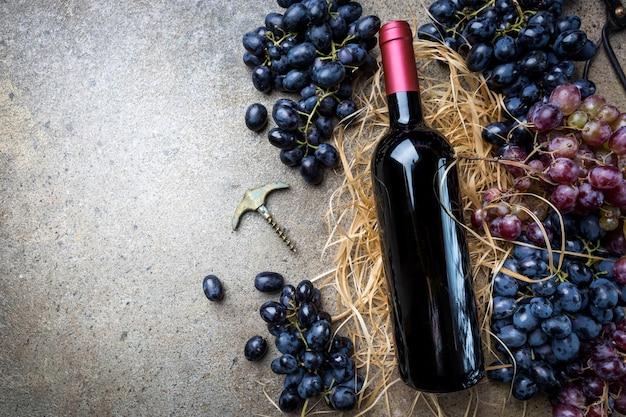 灰色の石の上にブドウと赤ワインのボトル