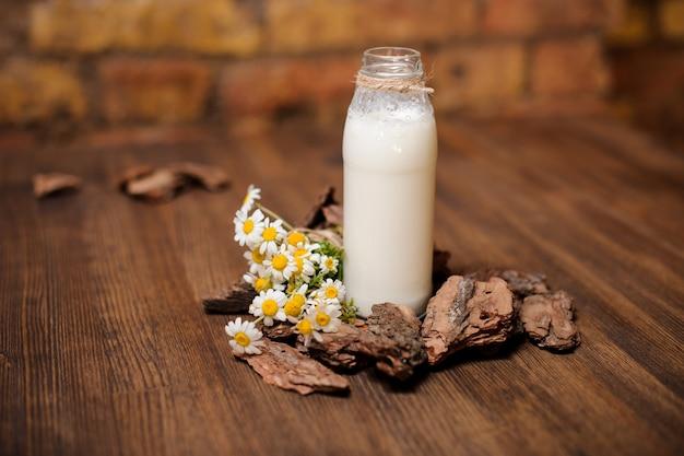 素朴な牛乳のボトルと木製のテーブルにカモミールの花束