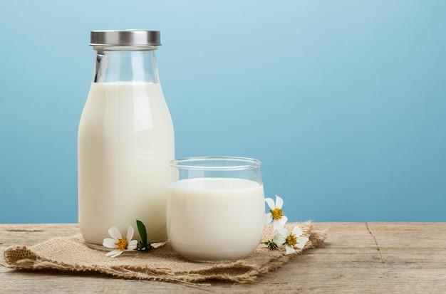 素朴な牛乳のボトルと青色の背景、おいしい、栄養価の高い、健康的な乳製品の木製テーブルの上の牛乳のガラス Premium写真