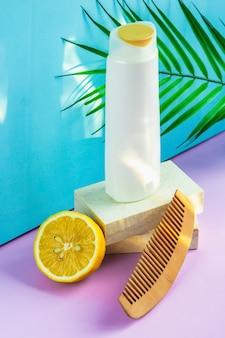 Бутылка шампуня, расческа и лимон