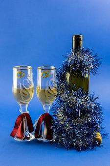 Бутылка игристого вина с двумя бокалами, украшенными новогодней мишурой.