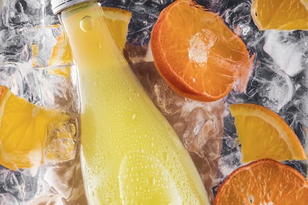 角氷とオレンジとフルーツのスライスを入れた水中の夏の新鮮な冷たいソーダレモネードのボトル。フラットレイ水滴。